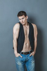 muscle concept - embarrassed young man putting his big muscular arms in his jeans pockets to hide his muscles and bare chest,studio shot,low contrast effect