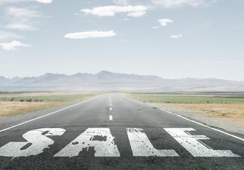 Sale word on asphalt road