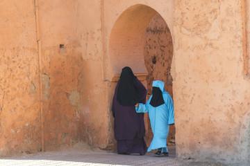 Muslim women entering a doorway in Morocco