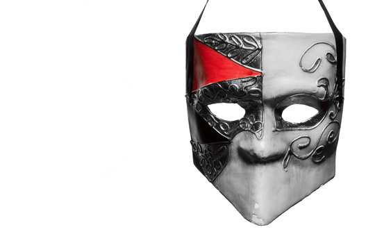 Venetian style masquerade mask in black and white with a bit of red hanging in front of a white background