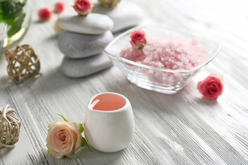 Composition of flowers, salt and stones on white wooden background, in spa salon