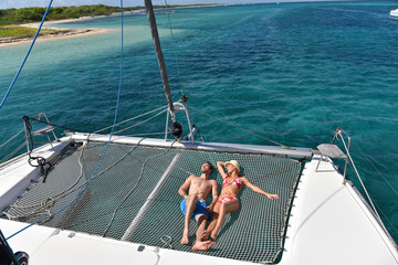 Couple suntanning on a catamaran net