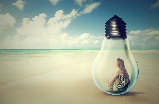 woman sitting inside a light bulb on a beach looking at the ocean view