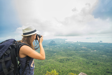 Travel concept. Young woman tourist - photographer taking photo at mountain peak