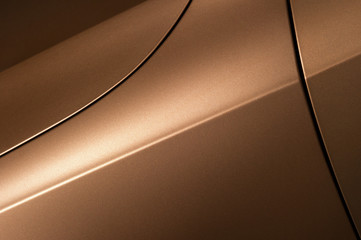 Surface of bronze sport sedan car, detail of metal hood, fender and door of vehicle bodywork