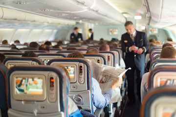 Steward and passengers on commercial airplane. Wall mural