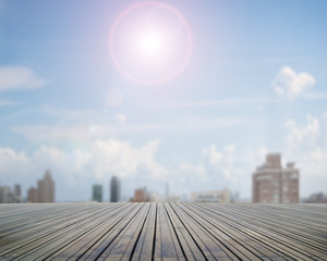 Wooden floor with sunny sky cityscape background
