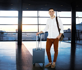 Young man with suitcase in hall of airport