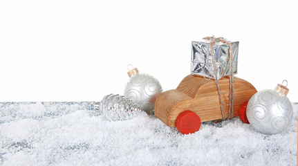 Wooden toy car with gift box and toys on a snowy table over white background