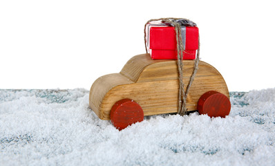 Wooden toy car with gift box on a snowy table over white background