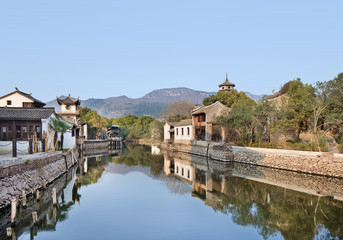 Ancient white Chinese houses reflected in a tranquil canal, Hengdian, China