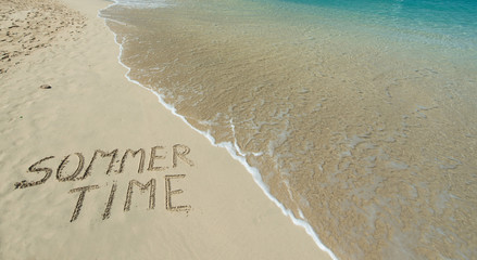 Summer time written in the sand