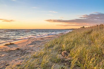 Summer Beach Background.  Remote beach bathed in golden light with sand dunes and dune grass. St. Ignace, Michigan.