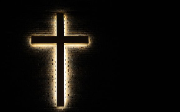 Lighted Cross Background. Back lit cross on a brick background with copy space.