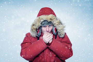 Man in winter clothes warming hands, cold, snow, blizzard