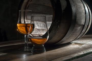 Two glasses of strong alcohol, amid oak barrels