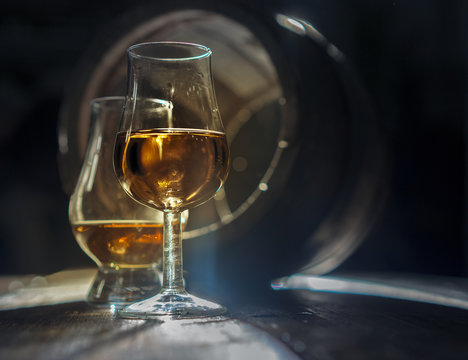 Two glasses of strong alcohol and oak barrel