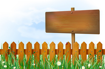 Wooden fence and sign on spring meadow