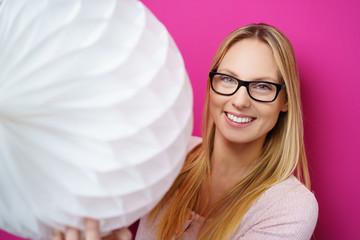 frau hält einen weißen pompon-ball aus papier in der hand