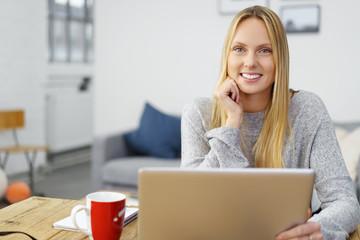 glückliche junge frau sitzt zuhause am laptop