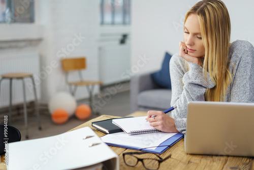 studentin sitzt zuhause am tisch und macht sich notizen