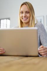 frau sitzt zuhause am tisch und arbeitet am laptop