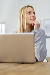 frau sitzt zuhause am laptop und schaut in gedanken zur seite