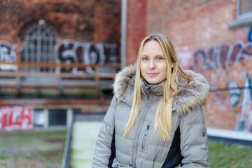 frau steht vor einem alten industriegebäude mit grafitti