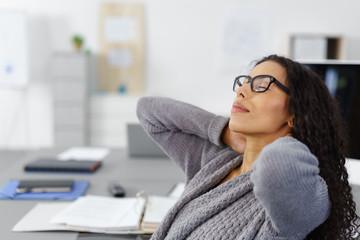 frau im büro dehnt ihren nacken nach langer arbeit