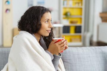frau genießt eine tasse warmen tee zu hause auf dem sofa