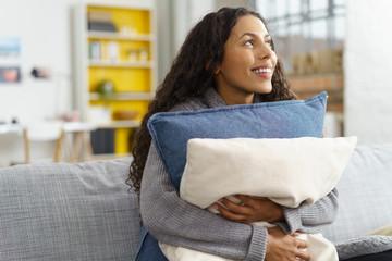 lachende frau umarmt ihre sofakissen