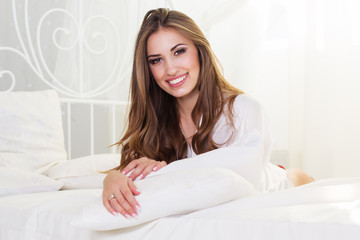 Smiling woman is lying in bed