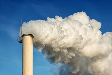 factory chimney and smokestack on blue sky background