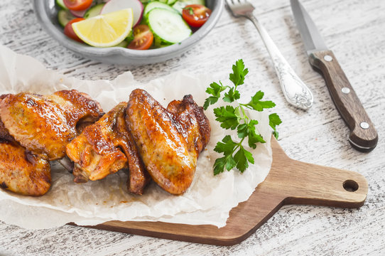 Spicy chicken wings and fresh vegetable salad on wooden white background