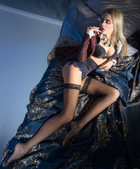 Woman in beautiful lingerie and a red jacket, lying in bed