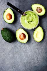 Guacamole with avocado. Halved avocado over black background wit