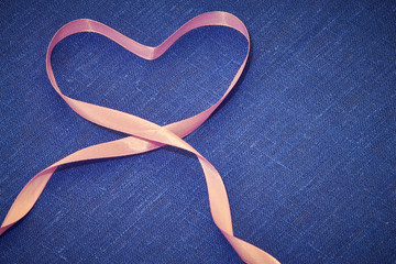 Heart of pink ribbon on blue linen cloth