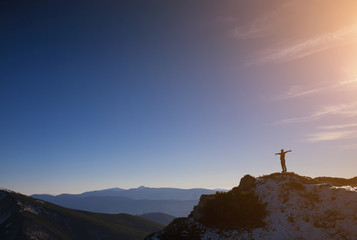 The silhouette of a man in the mountains.