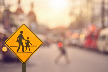 School sign on blur traffic road background.