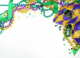 Mardi Gras image of harlequin mask, beads, ribbon and confetti in gold, green and purple