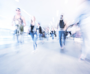 Zoom and motion blurred crowd walking in city