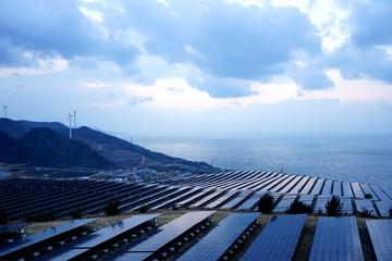 大きなソーラーパネルが並ぶ メガソーラー 太陽光発電所 / Solar panels and wind generators in Large Photovoltaic power station (solar park)