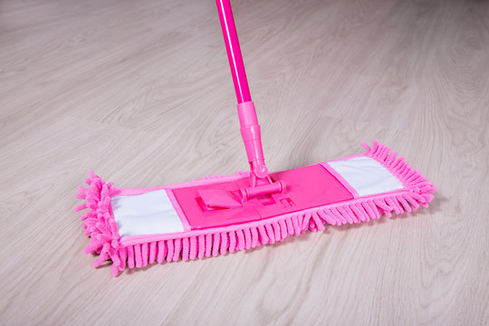 close up of wooden floor with pink mop