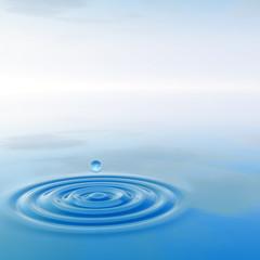 Conceptual blue liquid drop falling in water