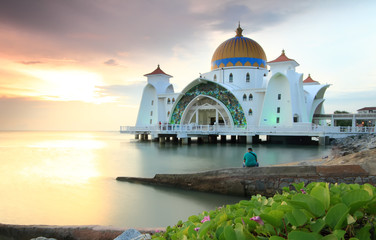 Man looking at the Majestic view of Malacca Straits Mosque during sunset. Wall mural