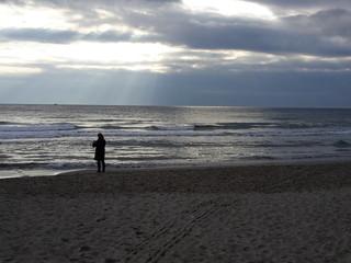 Donna sola in spiaggia con nubi e riflessi del sole