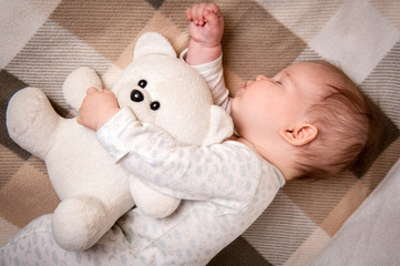 Newborn sweet child sleeping with teddy bear