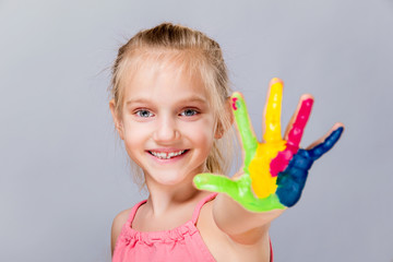 Colorful painted hands in a beautiful young girl.