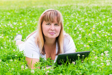 female 50 years lies with a tablet in a flower meadow