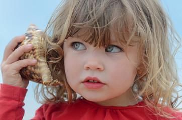très jolie fille écoutant la mer